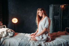 Young sick woman sitting on hospital bed Stock Photography