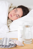 Young sick woman sleeping and pills on the table Royalty Free Stock Photo