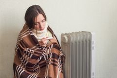 Young sick woman in woolen warm plaid checking her temperature with a thermometer at home. royalty free stock image