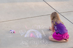 Young sidewalk artist. A young girl makes a chalk design on a light pavement. Room at the top for copy text Stock Images