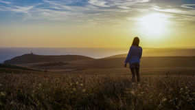 Young silhouette woman stands in a field looking into the sunset and distance Royalty Free Stock Images