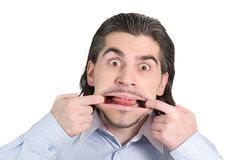 Young silly handsome male pulls faces. Young handsome guy pulling faces isolated on white Stock Image