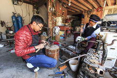 Young silversmith working on his workshop along with another woman dressed with the traditional Bai attire. Heqing: China - March 16, 2016: Young silversmith Royalty Free Stock Photos
