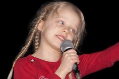 Young singer. Young girl singing into a microphone on black background Royalty Free Stock Photos
