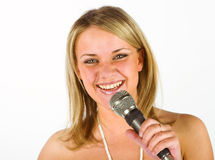 Young singer. Young woman with a microphone royalty free stock photography
