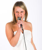 Young singer. Young woman with microphone royalty free stock images