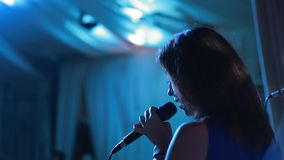Young singer with a microphone. Close up portrait of attractive young singer with a microphone stock footage
