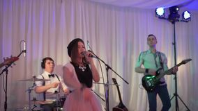 The young singer performs at the festival. The girl is singing at the wedding. Performance rock group at the event. HD stock video footage
