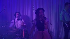 The young singer performs at the festival. The girl is singing at the wedding. Performance rock group at the event. A pretty girl is singing at a wedding stock video footage