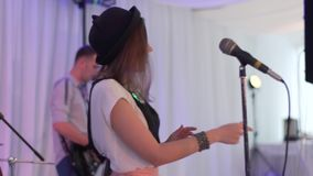The young singer performs at the festival. The girl is singing at the wedding. Performance rock group at the event. HD stock video