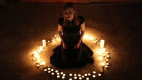 The girl sits on the floor among the burning candles. The young singer placed burning candles in a circle and sings a song stock footage
