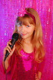 Young singer on the stage. Young girl in pink shiny dress singing with microphone on the stage stock image