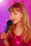 Young singer on the stage. Young girl in pink shiny dress singing with microphone on the stage Royalty Free Stock Images