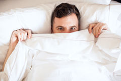 Young single man lying in bed. Portrait of a young man pulling the sheets of his bed up and peeking over them Royalty Free Stock Photo