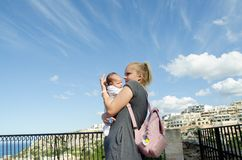 Young single mom holding one month old baby boy, worried face expression. Mellieha, Malta royalty free stock image