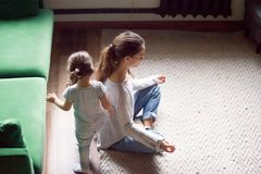 Young single mother doing yoga exercise while daughter playing. Young single mother doing yoga exercise, meditating while little preschool daughter running royalty free stock images