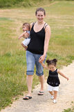 Young single mother family walking. Young single mother with her family walking on a trail stock images