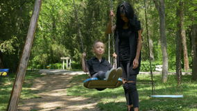 Young single mother pushing child on a swing set in park. Young single mother pushing child on a swing set stock video