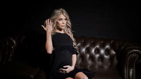 Young single pregnant woman in black dress sitting half-turn in the dark room on the big brown leather sofa looking at. The camera and touching her belly stock video