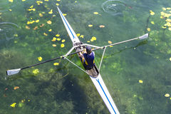 A Young single scull rowing competitor paddles on the tranquil l Stock Photo
