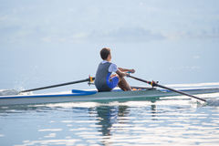 A Young single scull rowing competitor paddles on the tranquil lake Royalty Free Stock Photography