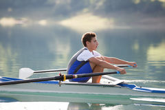 A Young single scull rowing competitor paddles on the tranquil lake Stock Photo