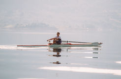A Young single scull rowing competitor paddles on the tranquil lake Stock Photography