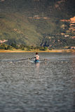 A Young single scull rowing competitor paddles on the tranquil lake Royalty Free Stock Image