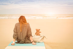 Young single woman sitting at beach with teddy bear. Looking at the sea - Solitude and loneliness concept with imaginary friendship and melancholic feelings royalty free stock images