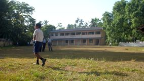 Young Sinhalese pupil walks along green playground. Colombo/Sri Lanka - April 05 2019: Young Sinhalese pupil walks along green playground grass holding cricket stock video footage