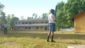 Young Sinhalese schoolboy holds blue cricket bat. Colombo/Sri Lanka - April 05 2019: Young Sinhalese schoolboy holds blue cricket bat on school playground stock footage