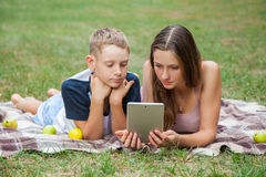 Young sister and brother lying down and work with tablet Stock Images