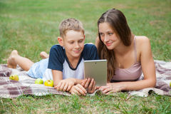Young sister and brother lying down and work with tablet Stock Photos