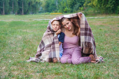 Young sister and brother stand covered with plaid in park. Royalty Free Stock Image