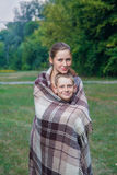 Young sister and brother stand covered with plaid in park. Royalty Free Stock Photo