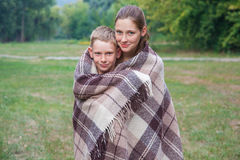 Young sister and brother stand covered with plaid in park. Stock Image