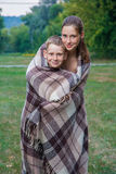 Young sister and brother stand covered with plaid in park. Stock Photos