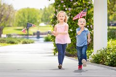 Young Sister and Brother Waving American Flags At The Park.  royalty free stock images