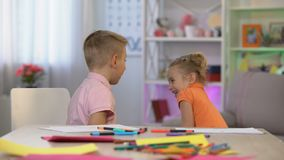 Young sister disturbing elder brother drawing table, family communication, fun. Stock footage stock video