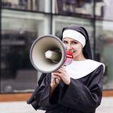 Surprised nun speak to megaphone outdoors. Stock Images