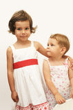 Young sisters. Portrait of two young sisters wearing white with red dresses Stock Photography