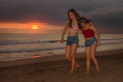 Young sisters or Asian Chinese girl at sunset beach with her best friend having fun enjoying Summer holidays trip together walkin stock images