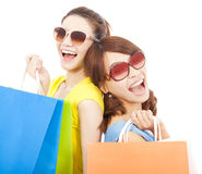 Young sisters holding shopping bags and Back to back Stock Photography