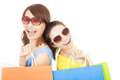 Young sisters holding shopping bags and Back to back Royalty Free Stock Images