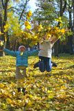 Young sisters jump on yellow leaves in autumn park. Happy childhood royalty free stock images