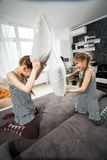 Young sisters pillow fighting on couch Stock Photography