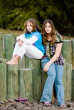Young sisters sad and depressed. Two sisters, ages 9 and 15, are sad, depressed, glum, or bored.  Background is a park setting.  Girls are multicultural and very Royalty Free Stock Images