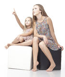 Young sisters watch together on something interesting. Royalty Free Stock Images