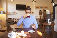 Young man sitting in coffee shop and working on digital tablet royalty free stock images