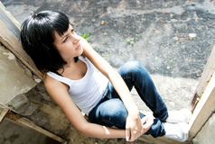 Young sitting sad woman from below Stock Image